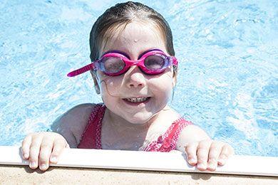 niña en la piscina de un hotel con parque acuático